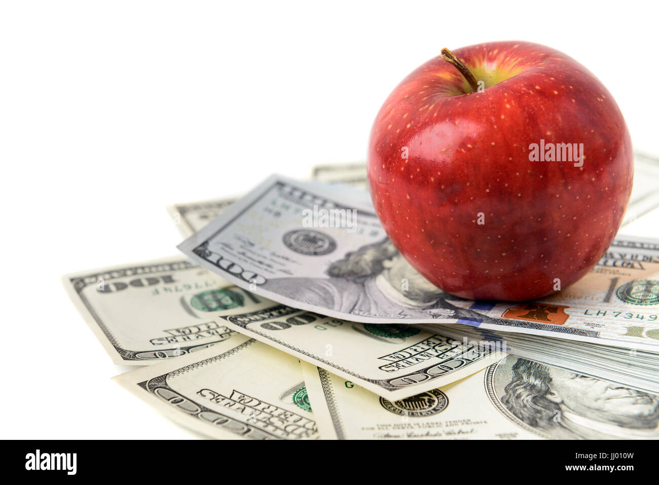 Dollars with red apple isolated on white - Stock Image