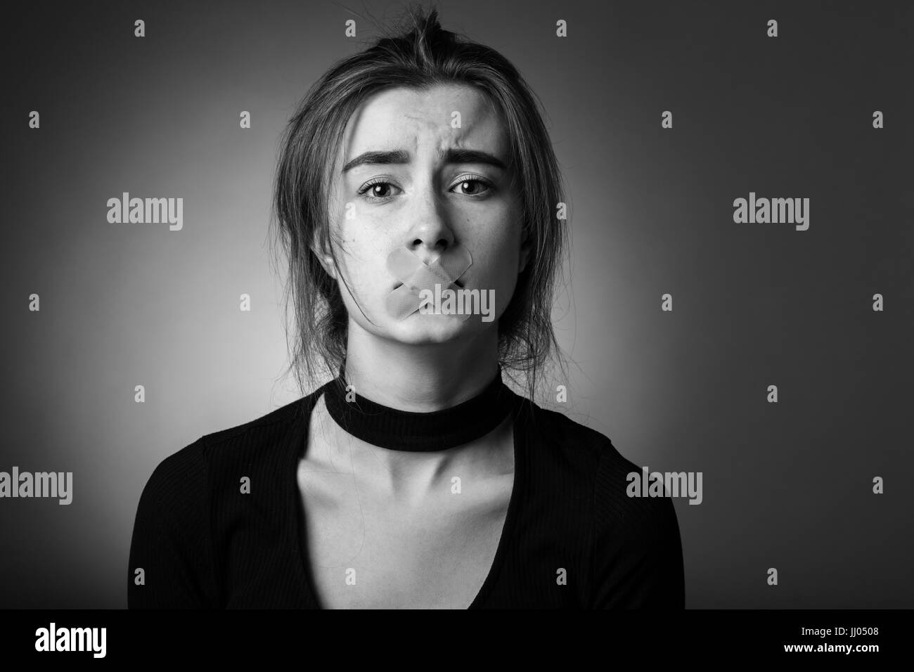 sad girl with plaster on her mouth looking at camera at gray background, monochrome Stock Photo