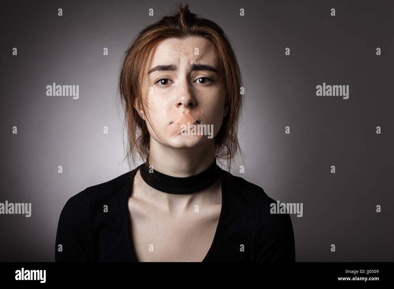 sad girl with plaster on her mouth looking at camera at gray background Stock Photo