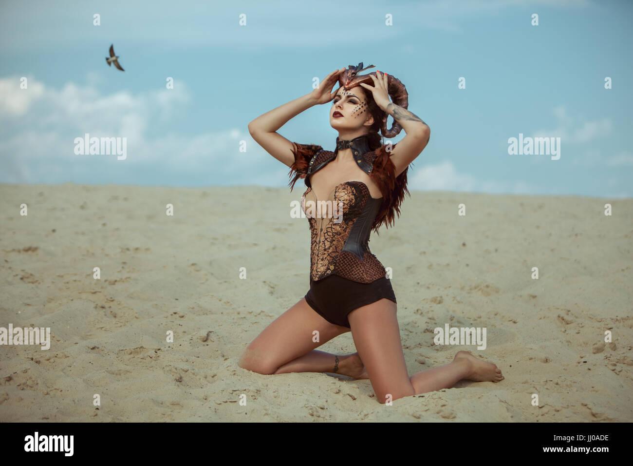 Horned woman in the desert kneeling on the sand. - Stock Image