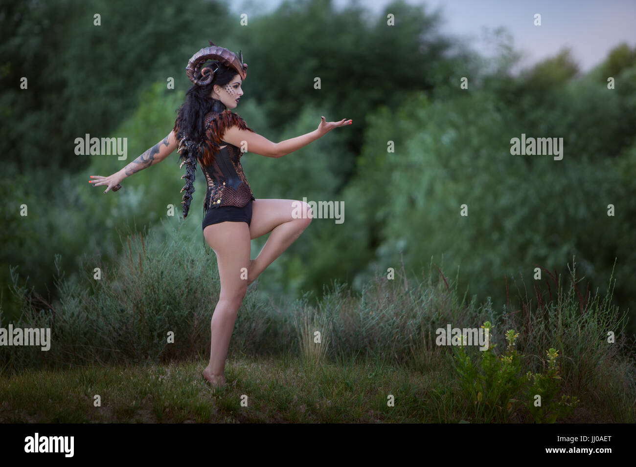 Modern wild woman with horns stands in the forest. - Stock Image