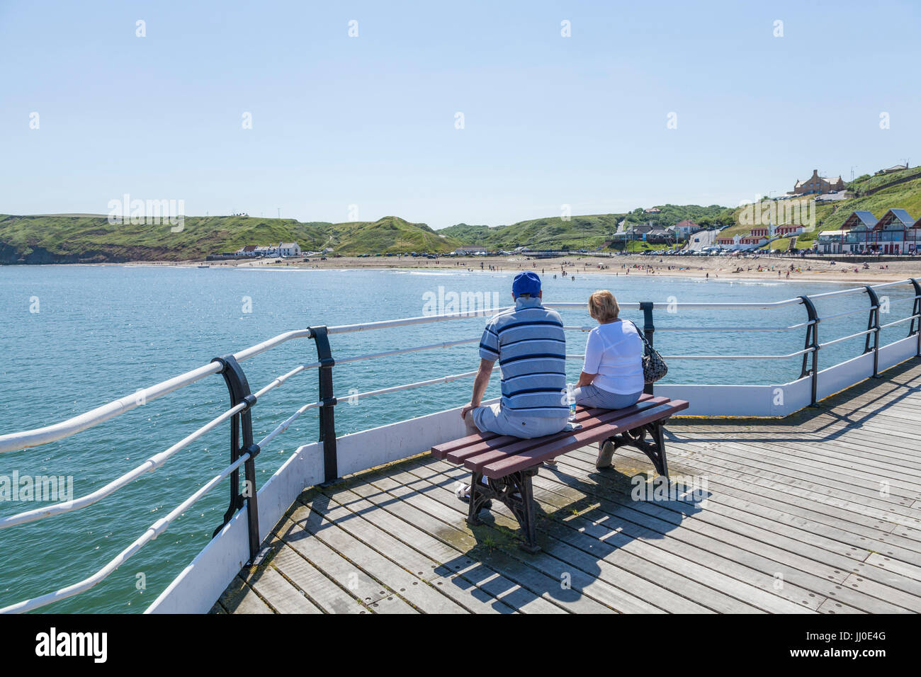A man and woman sat on a bench on the pier looking out to sea at Saltburn by the Sea,England,UK Stock Photo