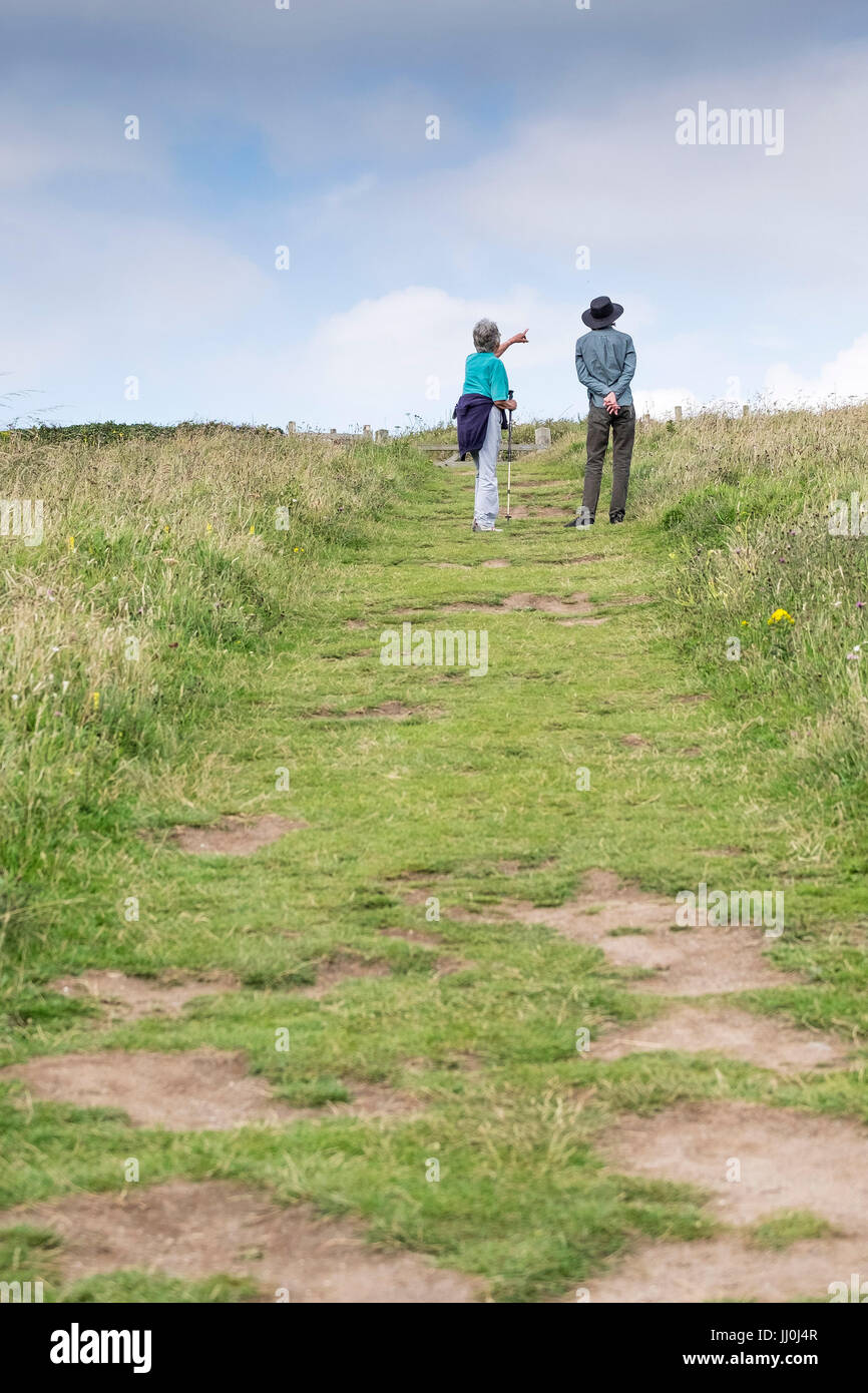 Two walkers pausing and looking at birds. - Stock Image