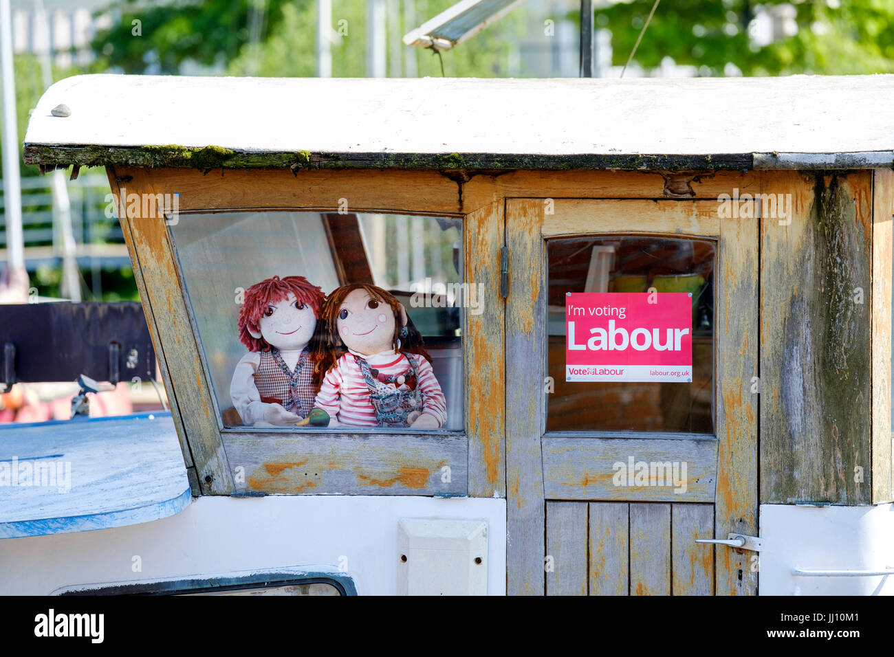 A vote Labour Party poster displayed on a boat in Bristol city docks, By its side are two Rosie and Jim children's - Stock Image