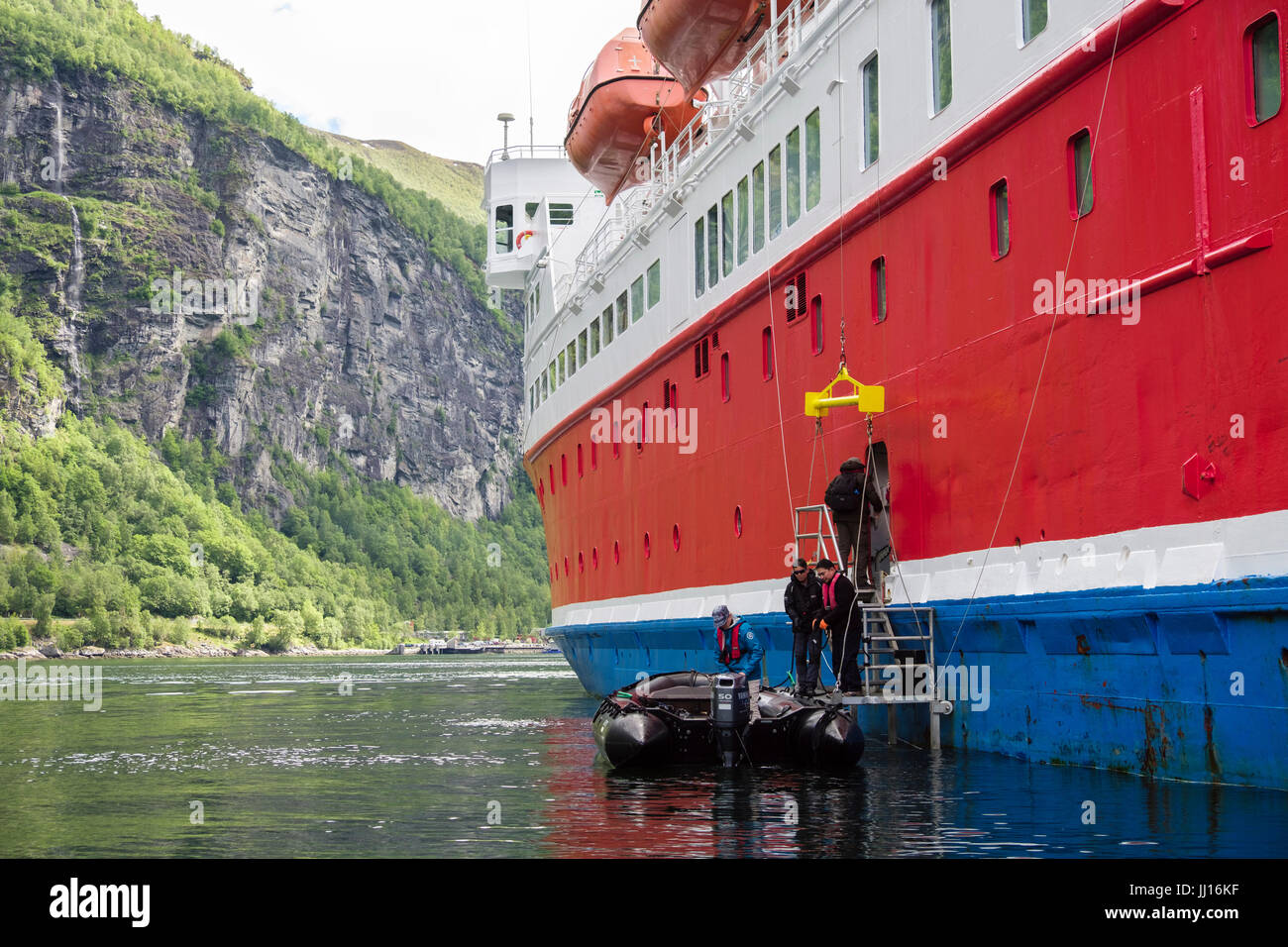 Passengers returning from Zodiac dinghy boat onto G Adventures Cruise ship Expedition in Geirangerfjorden. Geiranger - Stock Image