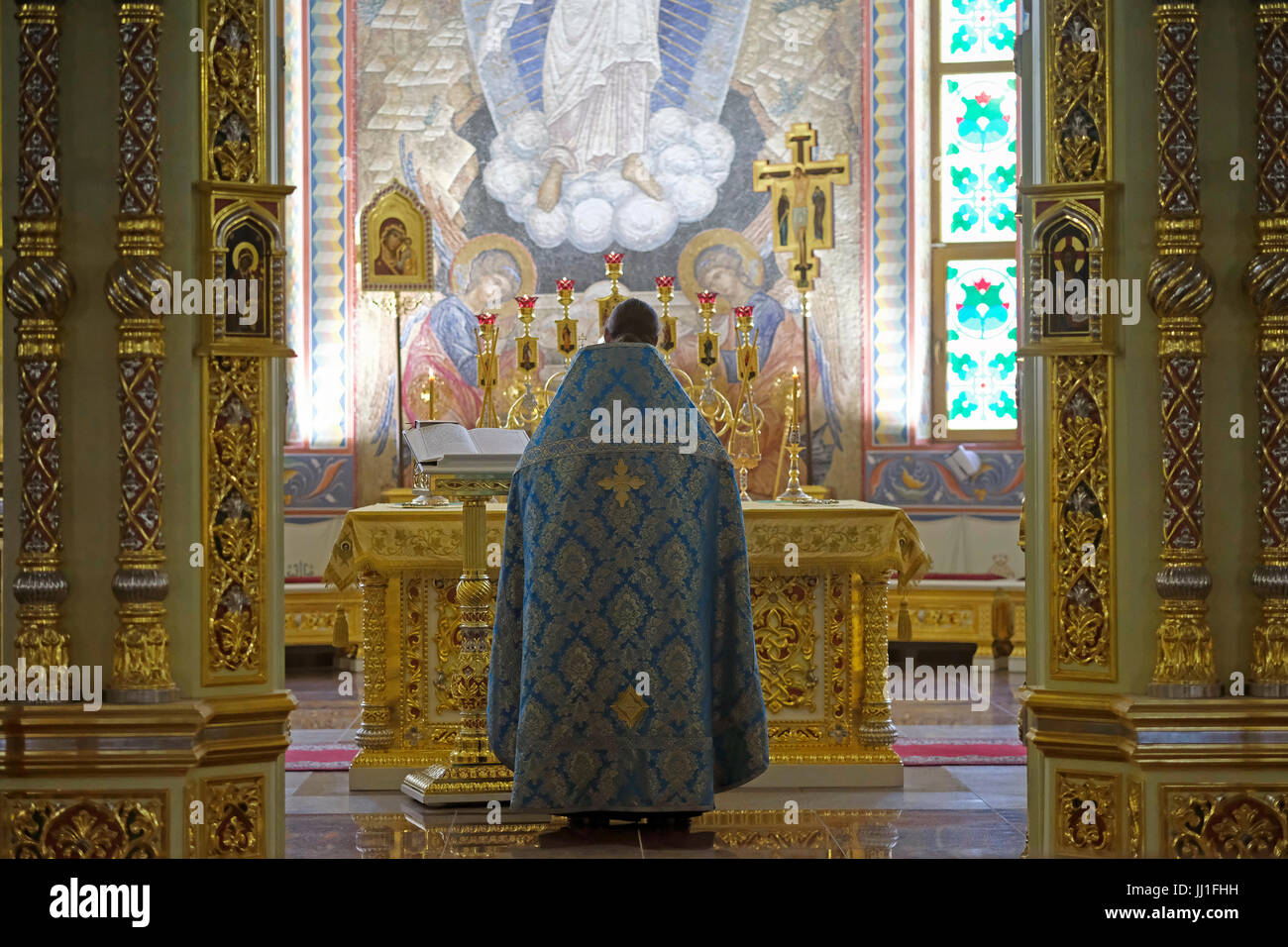 A Russian Orthodox priest praying at the altar of Cathedral of the Nativity in the city of Yuzhno-Sakhalinsk, on - Stock Image