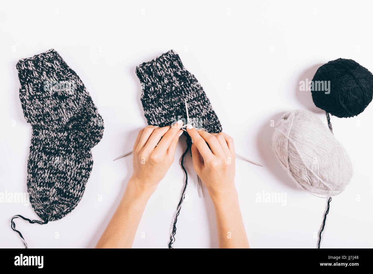 Female hands knit black wool socks on a white background, top view - Stock Image