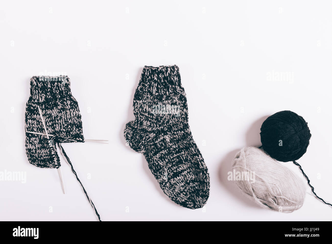 Black wool socks and balls of yarn laying on a white table, top view - Stock Image