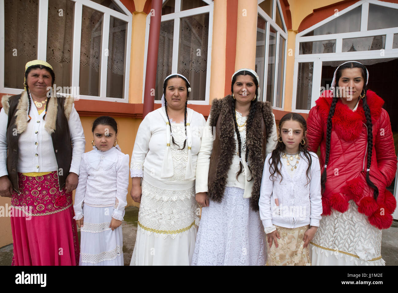 Women and girls of a Rom wealthy family in front of their luxury house, Ivanesti, Romania - Stock Image