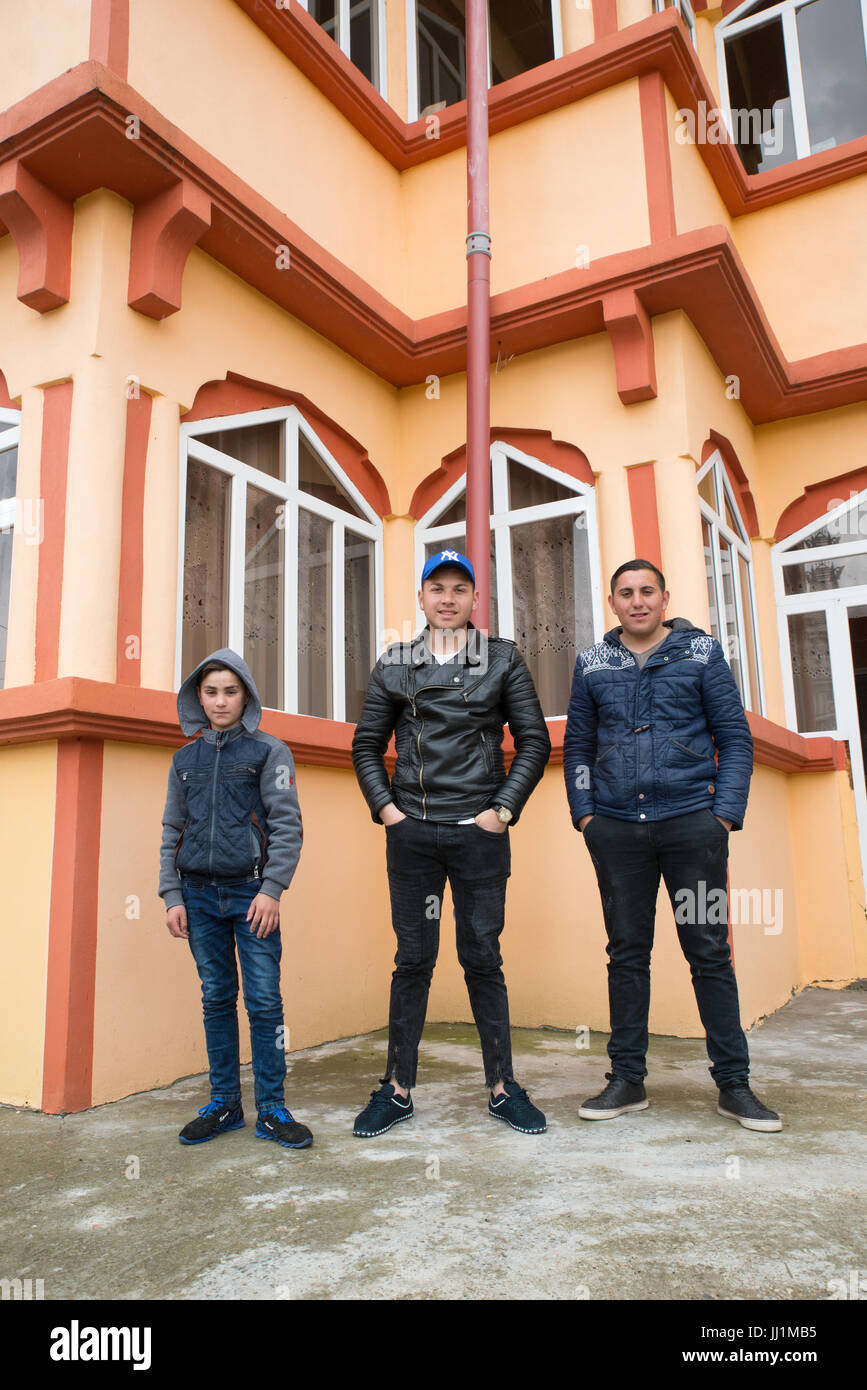 Three boys of a wealthy Roma gypsy family posing in front of their luxury house, Ivanesti, Romania - Stock Image