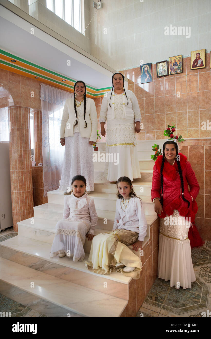 Women and girls of a wealthy Roma gypsy family posing on the staircase of their luxury house, Ivanesti, Romania - Stock Image