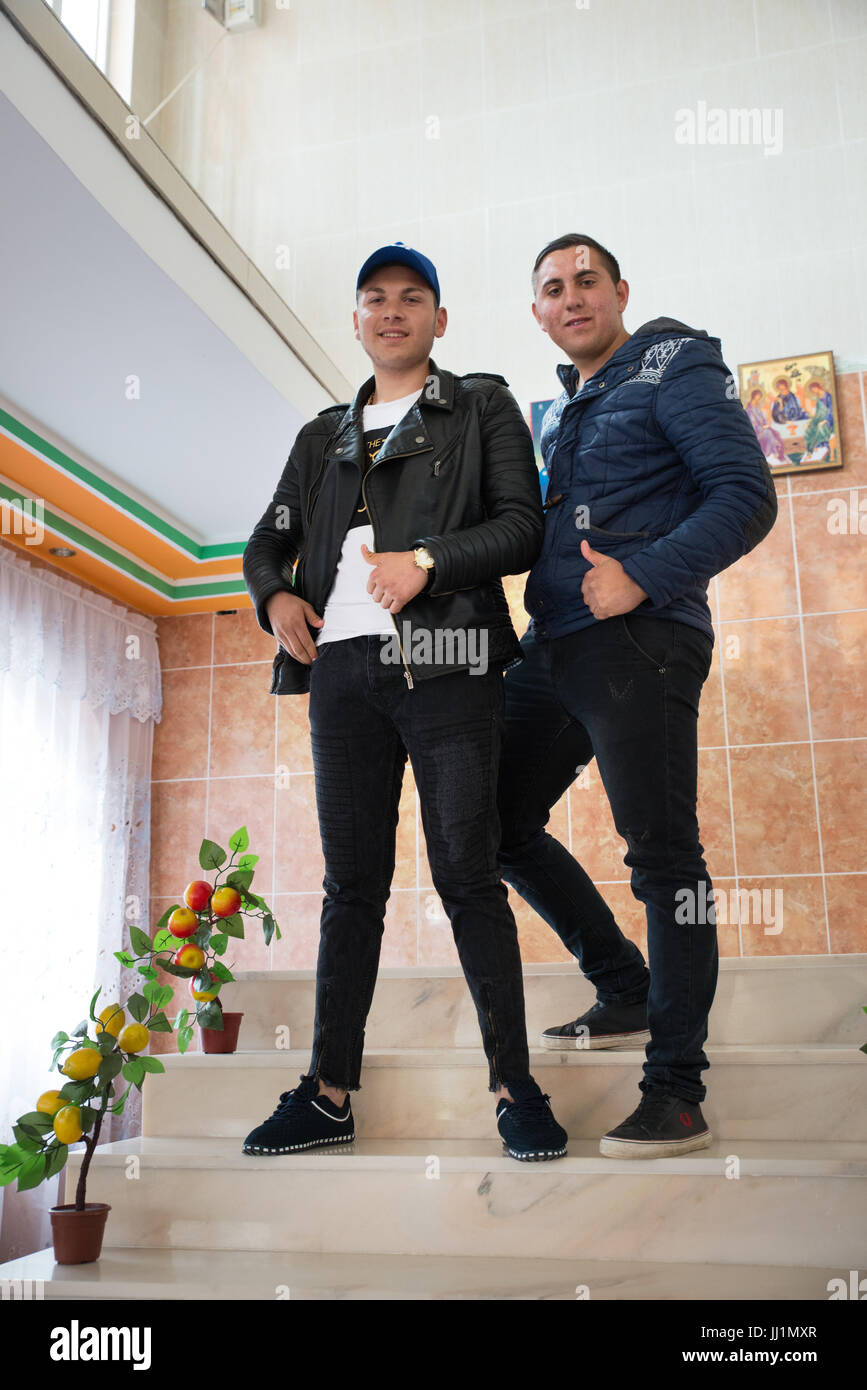 Two boys of a wealthy Roma gypsy family posing on the staircase of their luxury housey, Ivanesti, Romania Stock Photo