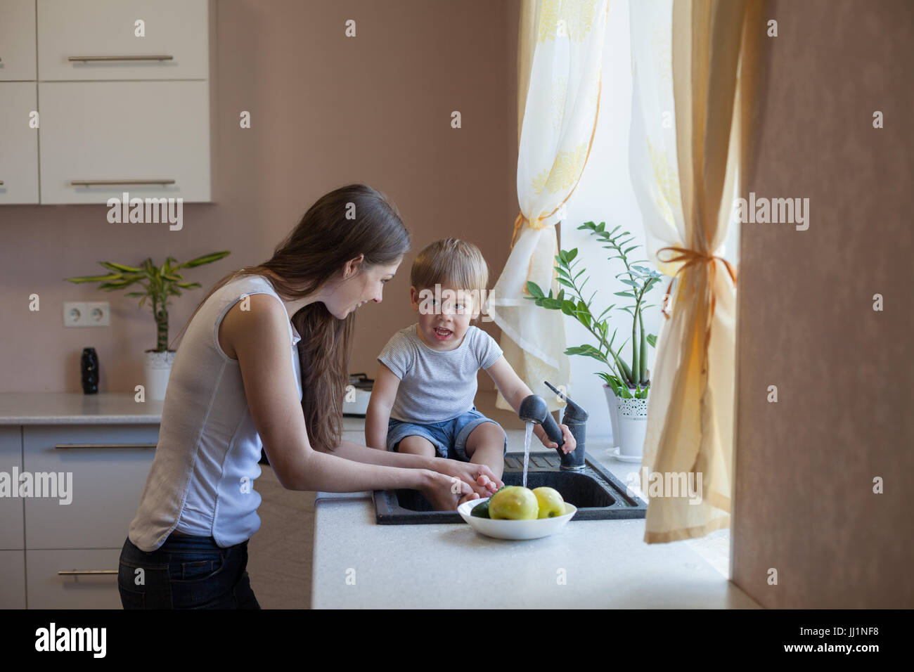 kitchen mom son wash fruits and vegetables - Stock Image