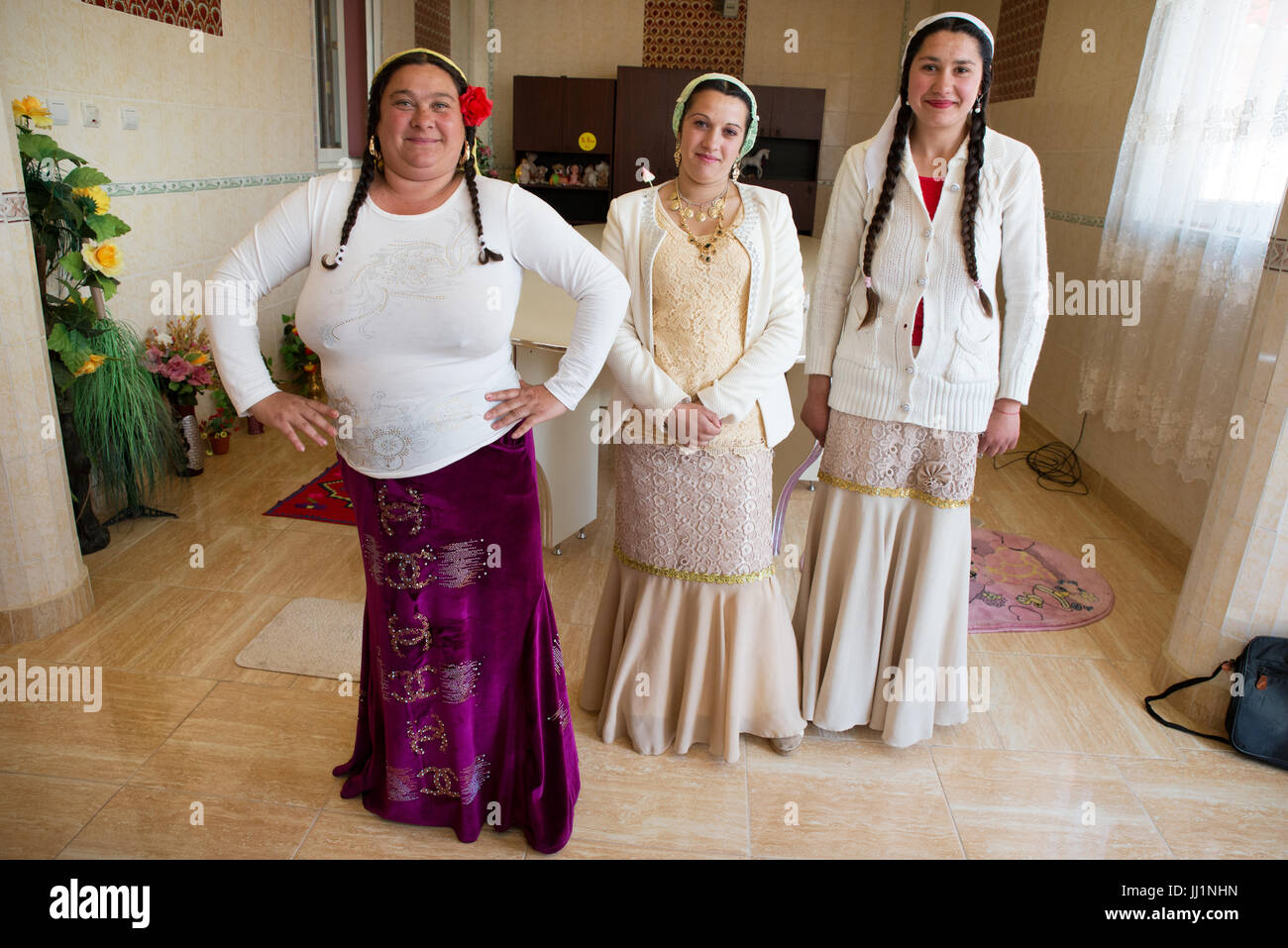 Three women of a wealthy Roma gypsy family posing inside their luxury house, Ivanesti, Romania - Stock Image
