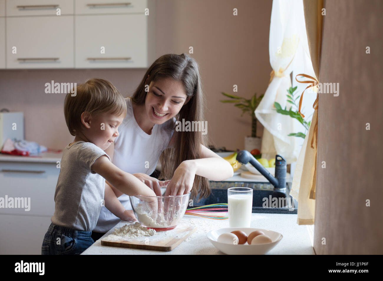 mother and son prepare pie with flour - Stock Image