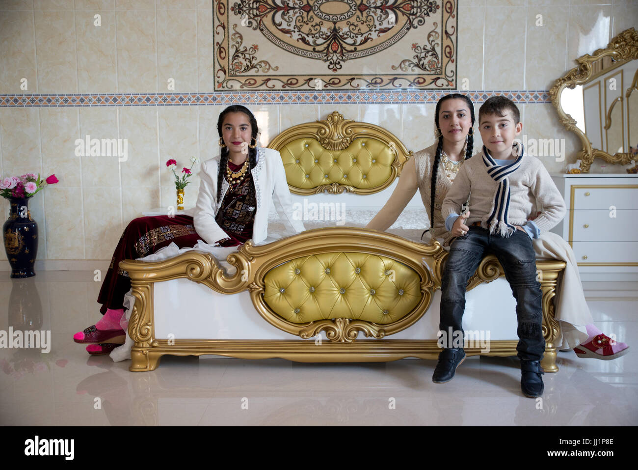 Kids of a wealthy Roma gypsy family posing in the luxurious bedroom of their house, Ivanesti, Romania - Stock Image