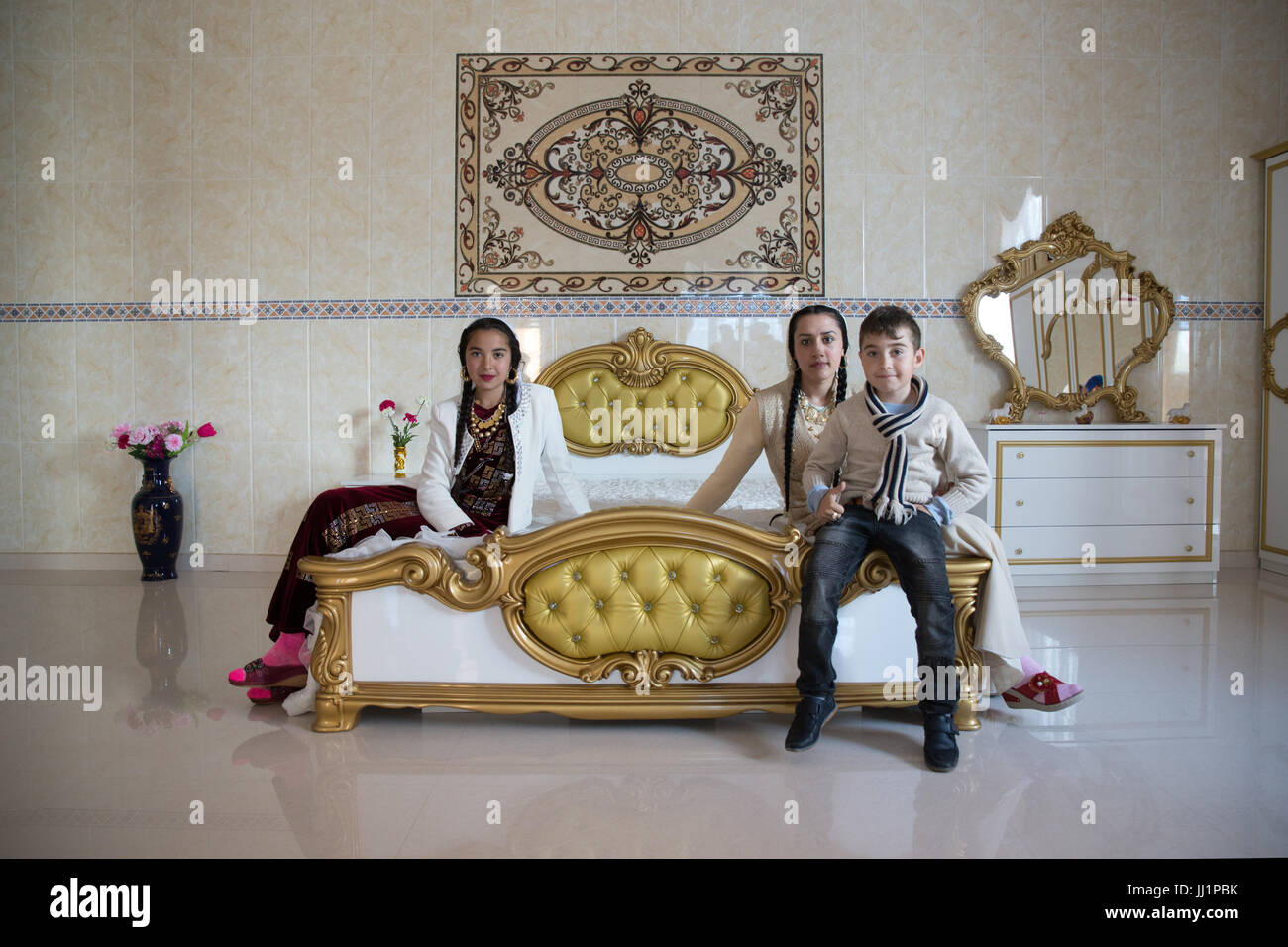 Kids of a wealthy Roma gypsy family posing in the luxurious bedroom of their house, Ivanesti, Romania Stock Photo