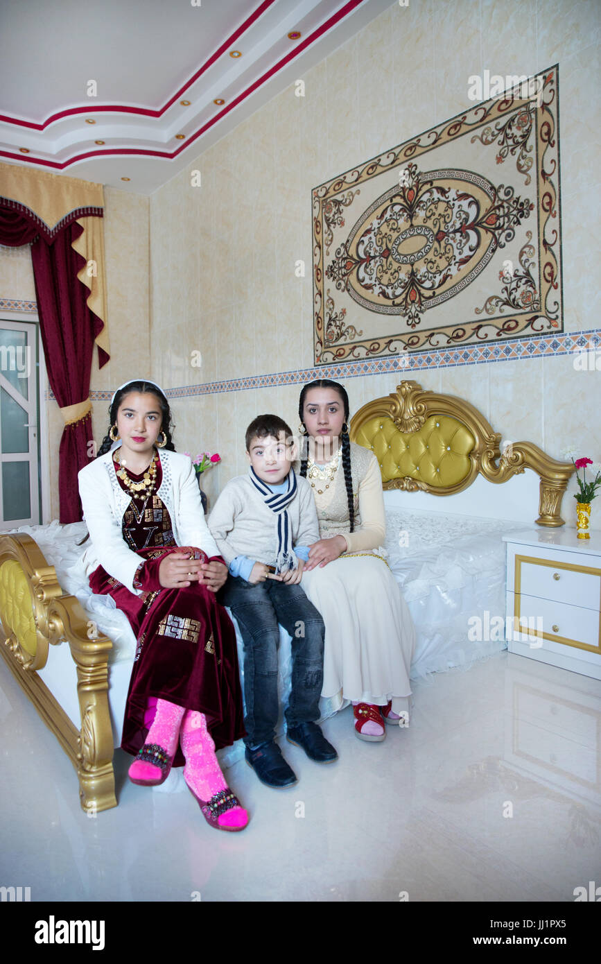 Girls of a wealthy Roma gypsy family posing in the luxurious bedroom of their house, Ivanesti, Romania - Stock Image