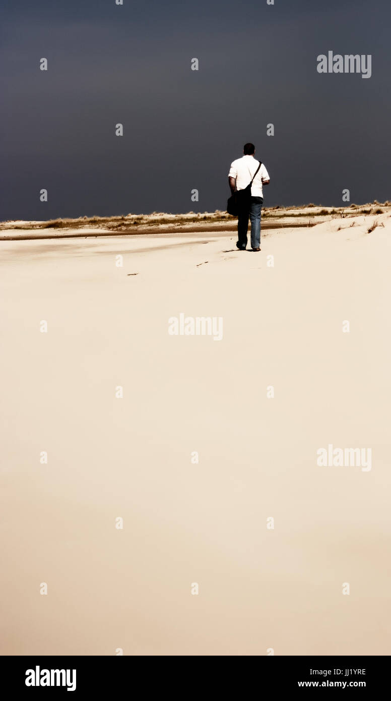 Young man is walking through the dunes, Nordeney, Germany. - Stock Image
