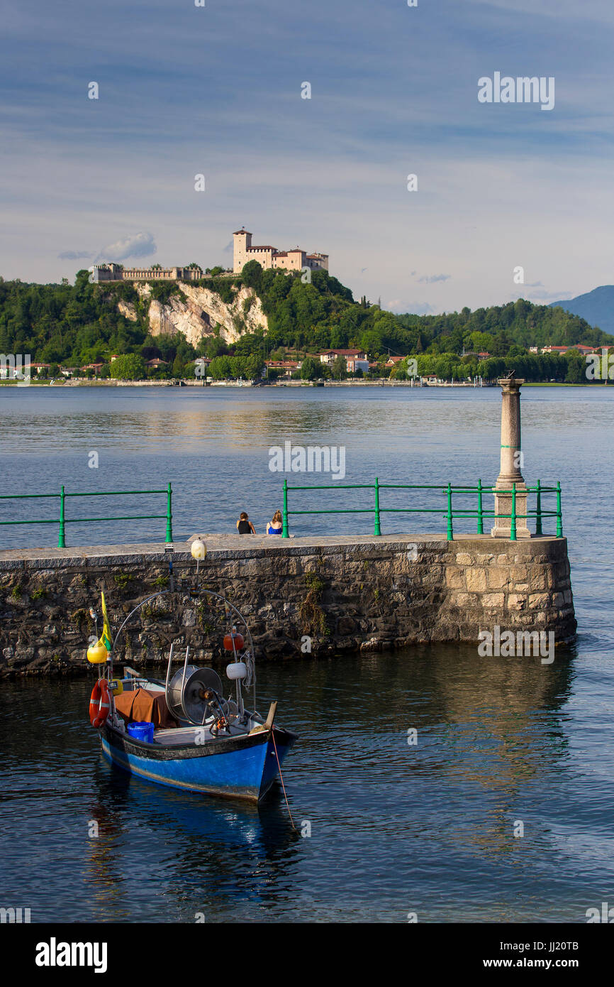 View of Angera Castle on Lake Maggiore taken from Arona with fishing boat and harbour wall. - Stock Image