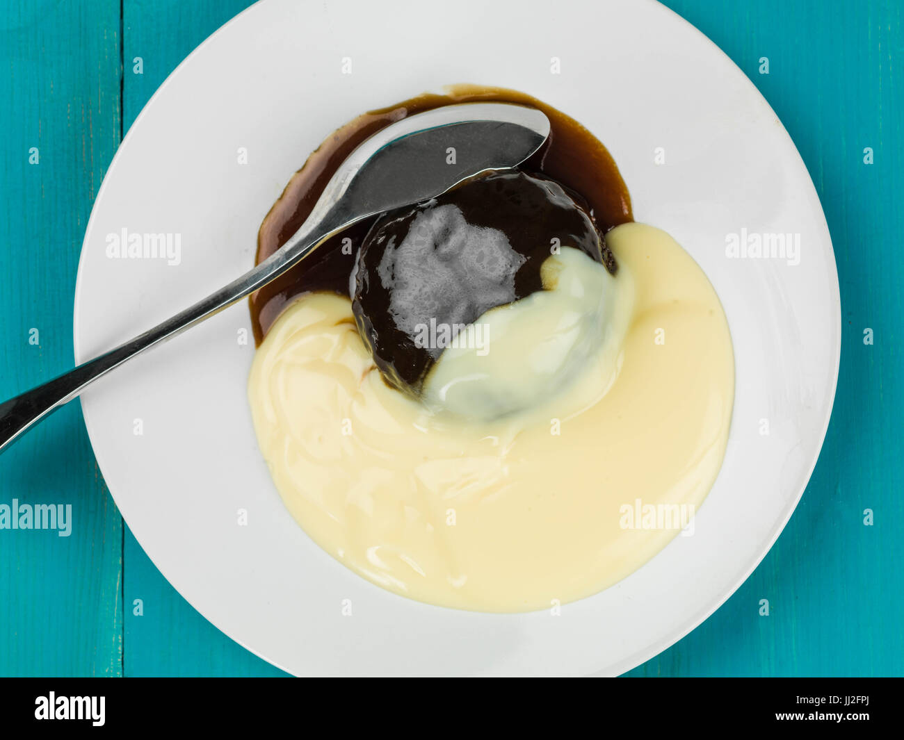 Sticky Toffee Pudding Dessert Served With Hot Custard Against a Blue Wooden Background - Stock Image