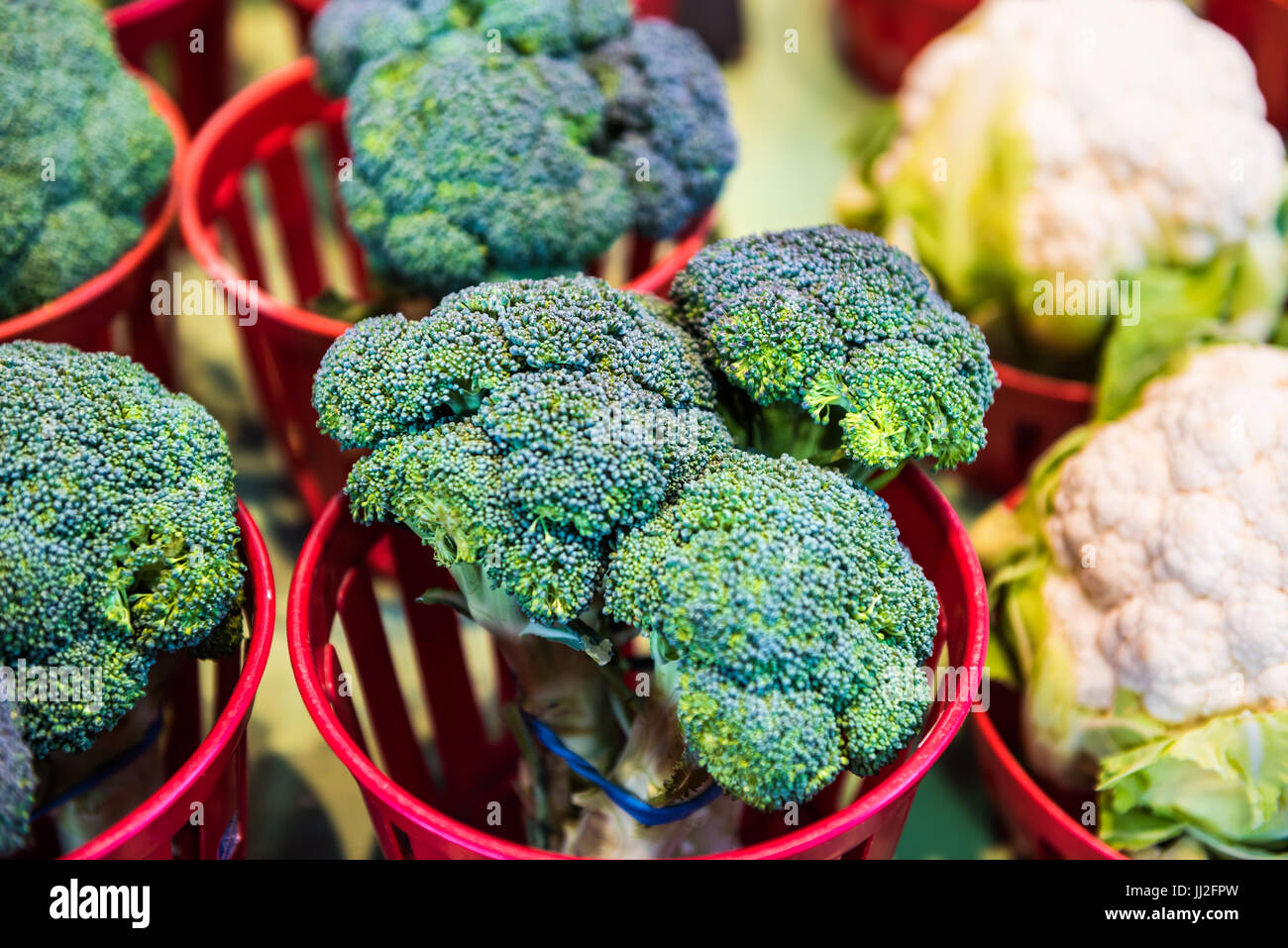 Closeup of broccoli and cauliflower bunches in baskets on display in farmers market - Stock Image