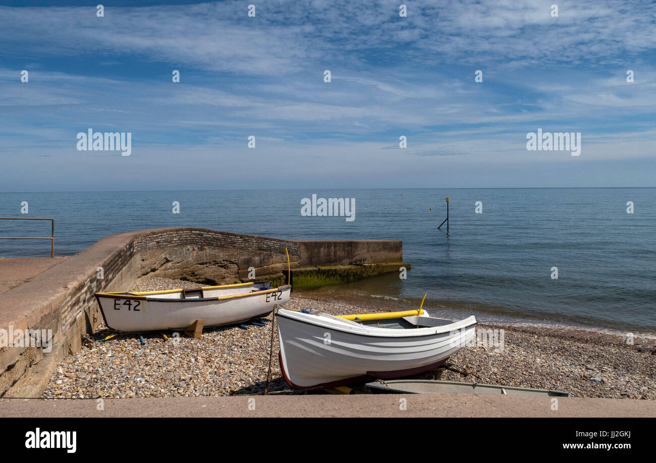 Fishing boats pulled up onto the shale pebble beach at Sidmouth,Devon, at the Port Royal area of the seafront. - Stock Image
