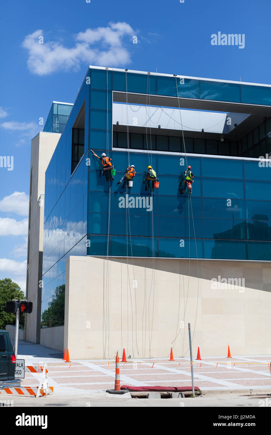 Four window washers on the outside of a building. - Stock Image