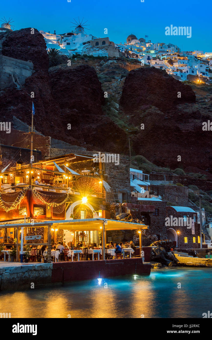 Night view of al fresco restaurant at Ammoudi port, Oia, Santorini, South Aegean, Greece - Stock Image