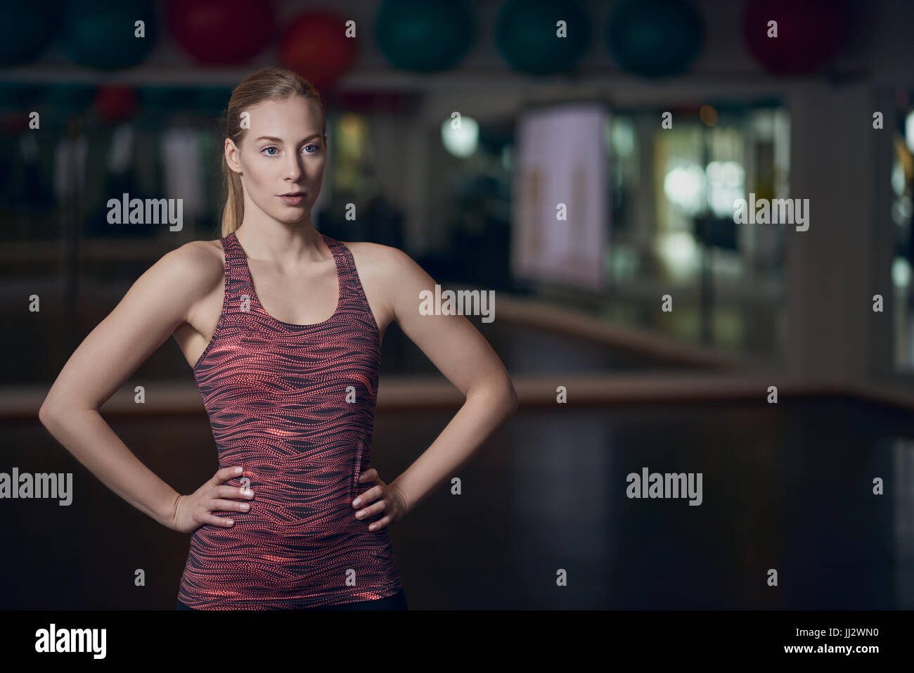 Three quarter body portrait of athletic young woman posing in gym with hands on hips - Stock Image