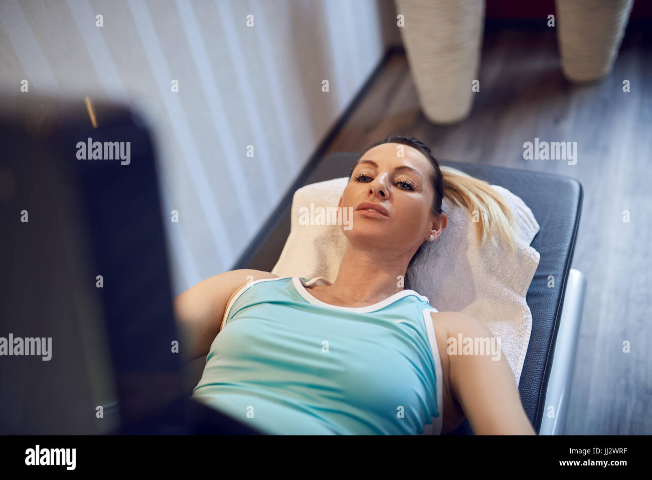 Attractive fit middle-aged woman doing vacuum therapy for prevention and strengthening of tissue - Stock Image