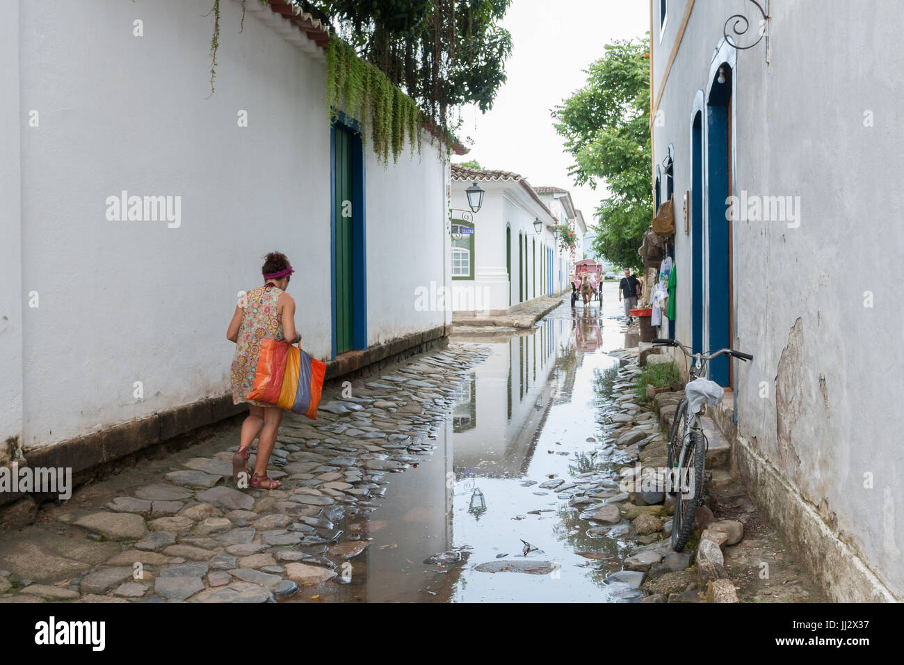 Woman walking on cobblestone street  flooded by incoming tide alongside colonial houses, Paraty, Rio de Janeiro, - Stock Image