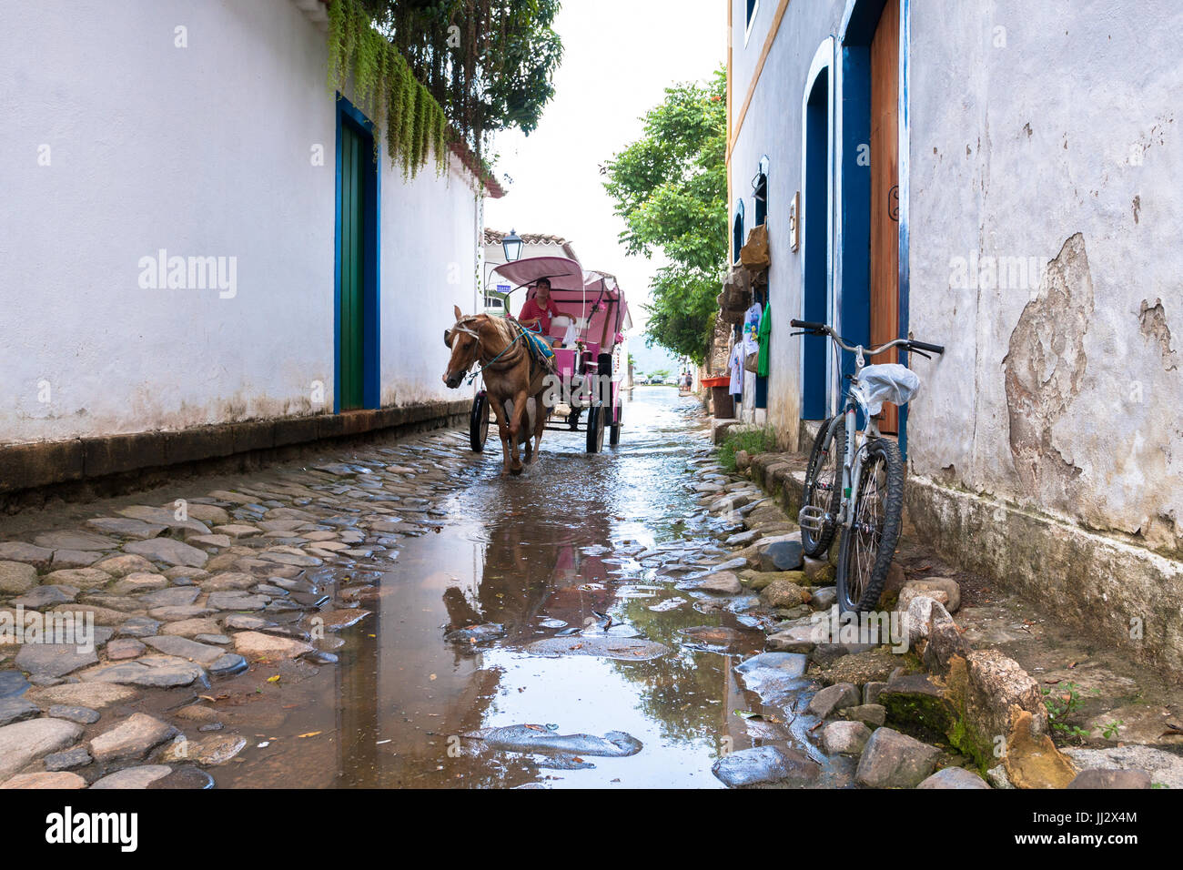 Horse pulls a cart along cobblestone street  flooded by incoming tide alongside colonial houses, Paraty, Rio de - Stock Image