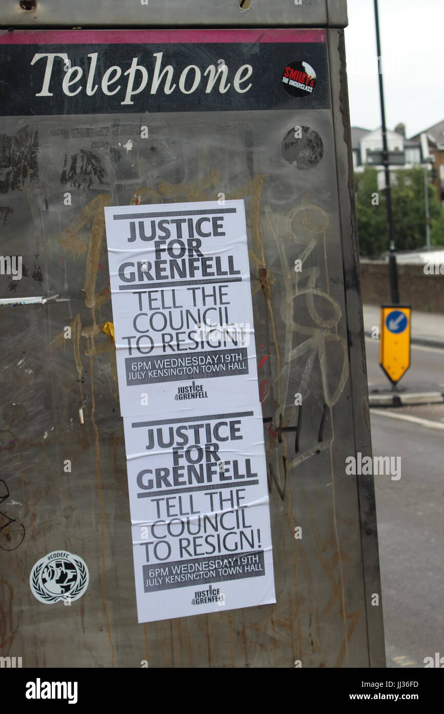 Justice for Grenfell posters advertising 19th July meeting to call on council to resign on side of telephone box - Stock Image