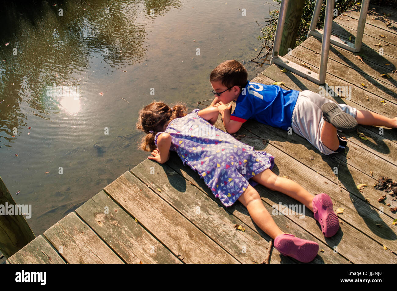 6-7 year old girl and boy looking over edge of dock - looking at fish. summer scenic - Stock Image