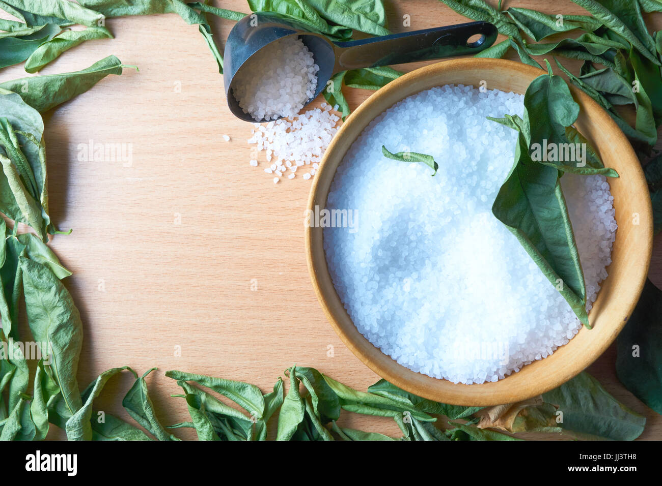 wooden bowl of sea salt with scoop framed by aromatic leaves. aroma therapy concept. copy space for title caption - Stock Image