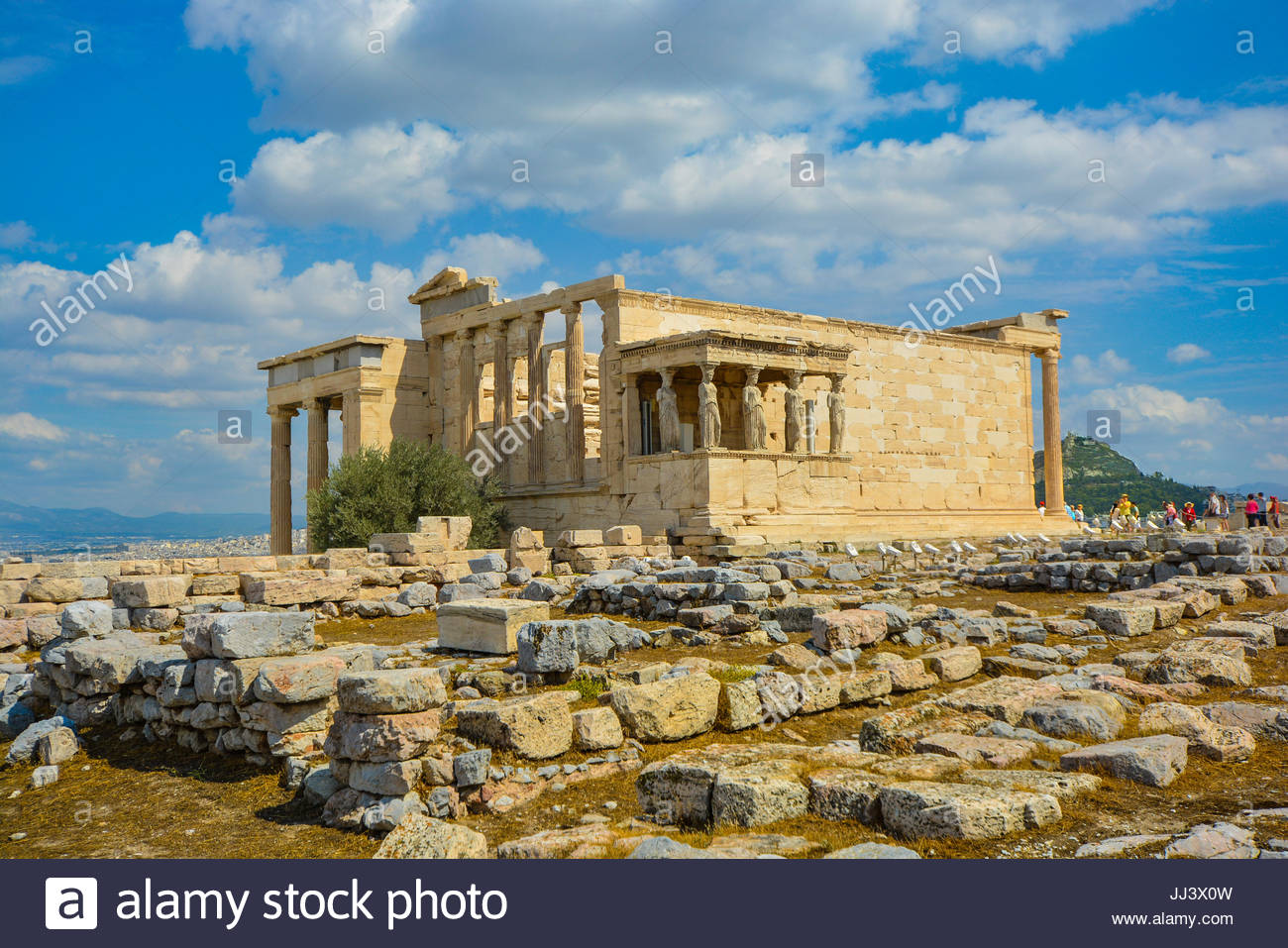View of the Erechtheion temple at the Athens Acropolis in Athens Greece on a warm summer day with Lykavittos Hill - Stock Image
