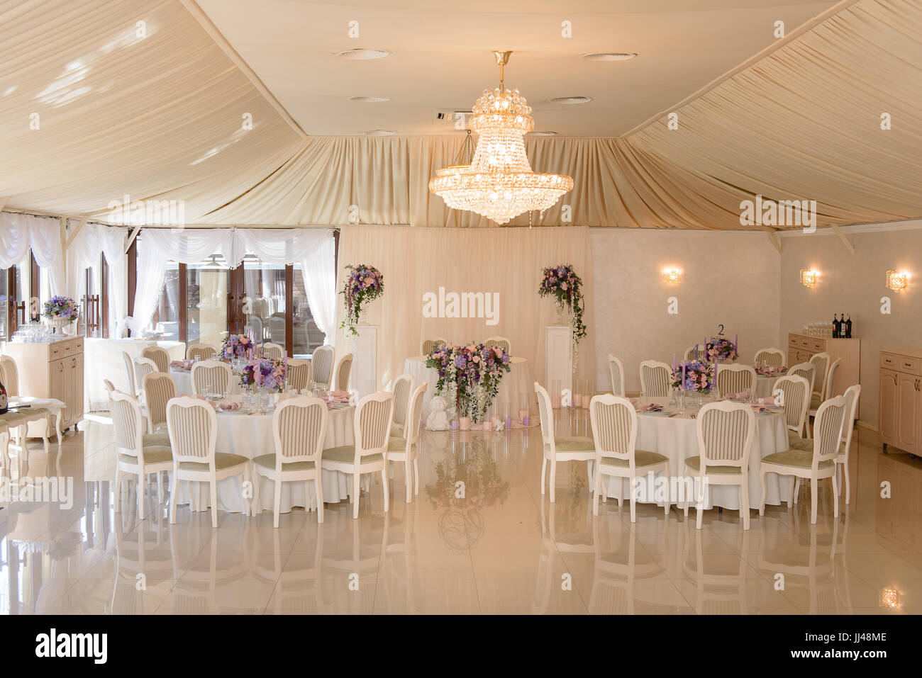 Interior of a wedding decorated restaurant in cream colors - Stock Image