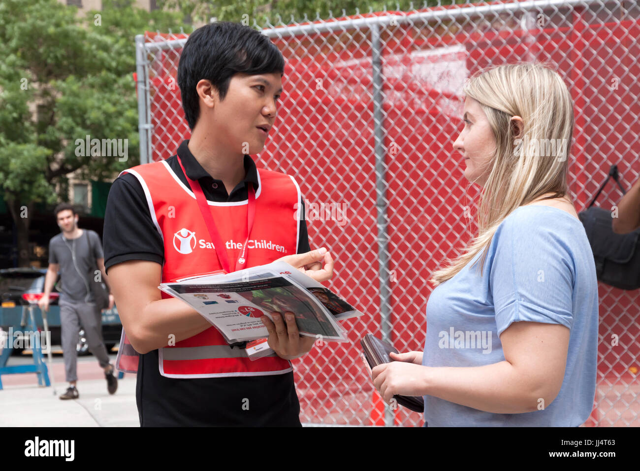 A canvasser for 'Save The Children' organization talks to a woman about recurring contributions (donations) - Stock Image