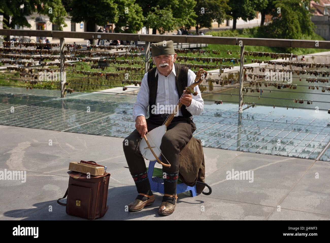 Old male street musician singing and playing a single stringed Gusle with bow on Butcher's Bridge over the Ljubljanica - Stock Image