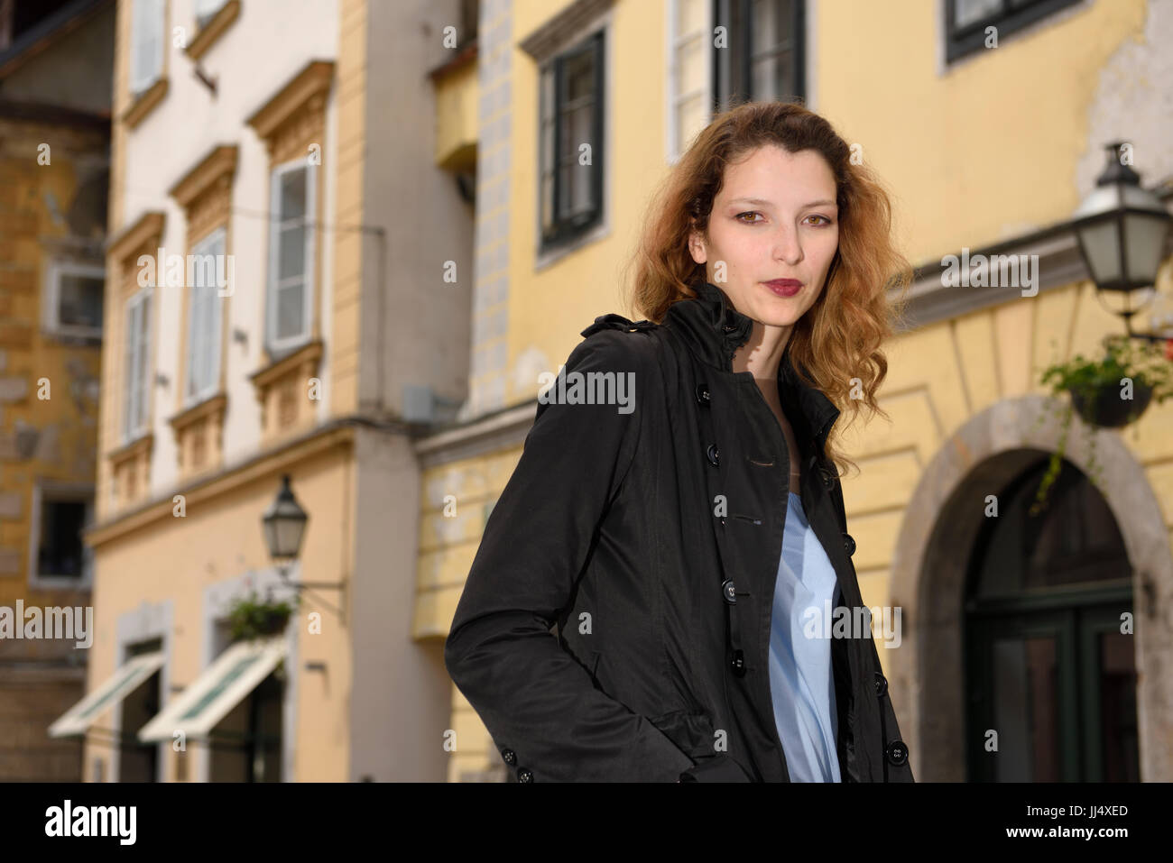 Young attractive female tourist with trench coat in Upper Square of the old town of Ljubljana Slovenia - Stock Image