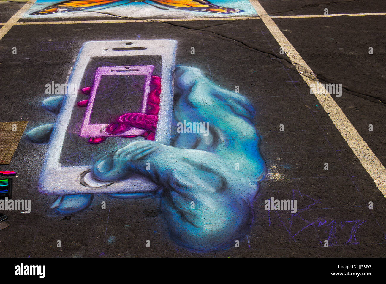 Chalk Rendition Of Hand Holding 3-D Cell Phones At Chalk The Walk Event - Stock Image