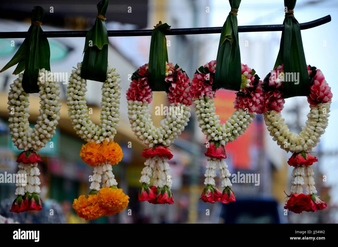 Jasmine and rose flower garlands hang with leaves in bazaar Hatyai Songkhla Thailand - Stock Image