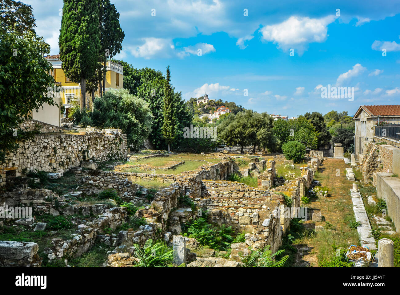 Ancient Greek ruins in Athens with a church and temple atop a hill in the distance on a warm summer day - Stock Image