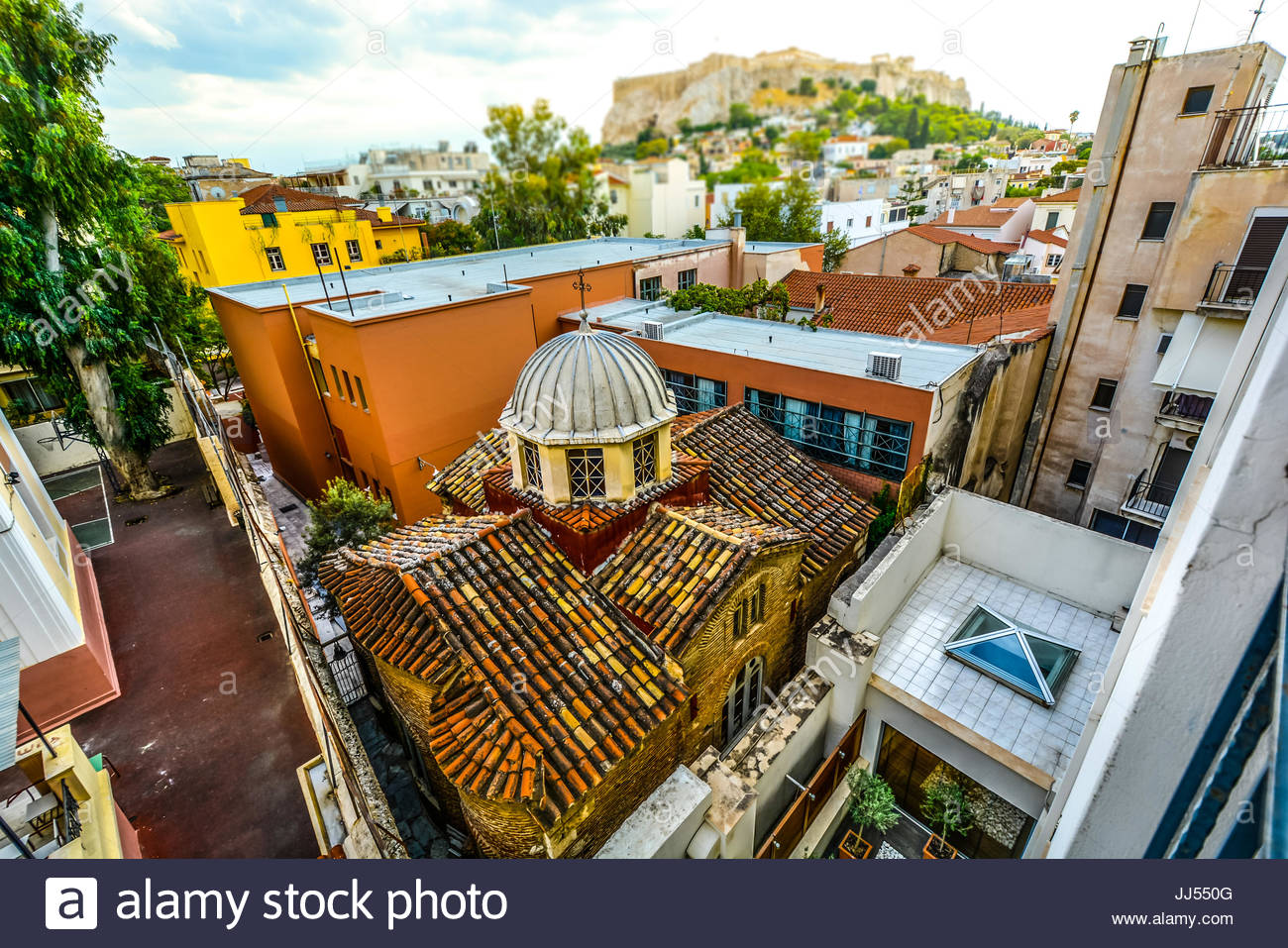 Window view of an ancient Church in Athens Greece squeezed in among the town buildings with the Acropolis and Parthenon - Stock Image