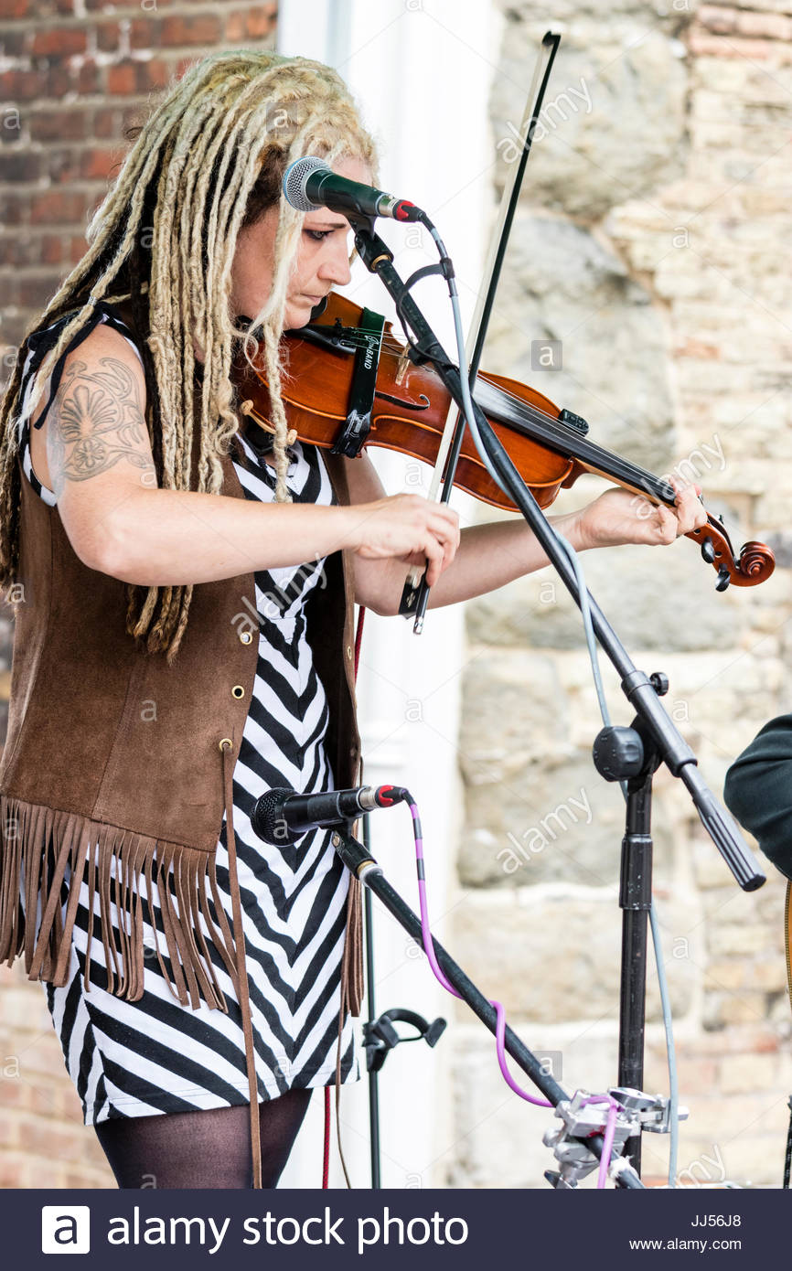Young blonde woman with dreadlock hair, Jo Carley from the folk music group Jo Carley and the old Dry Skulls, playing - Stock Image