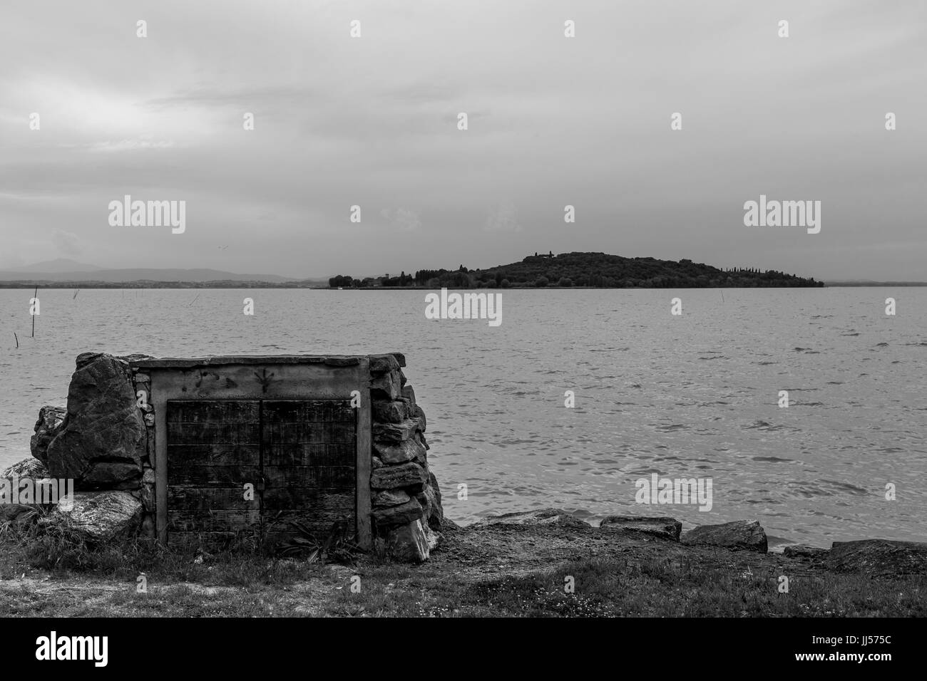 A lake shore with a closet built with some stones - Stock Image