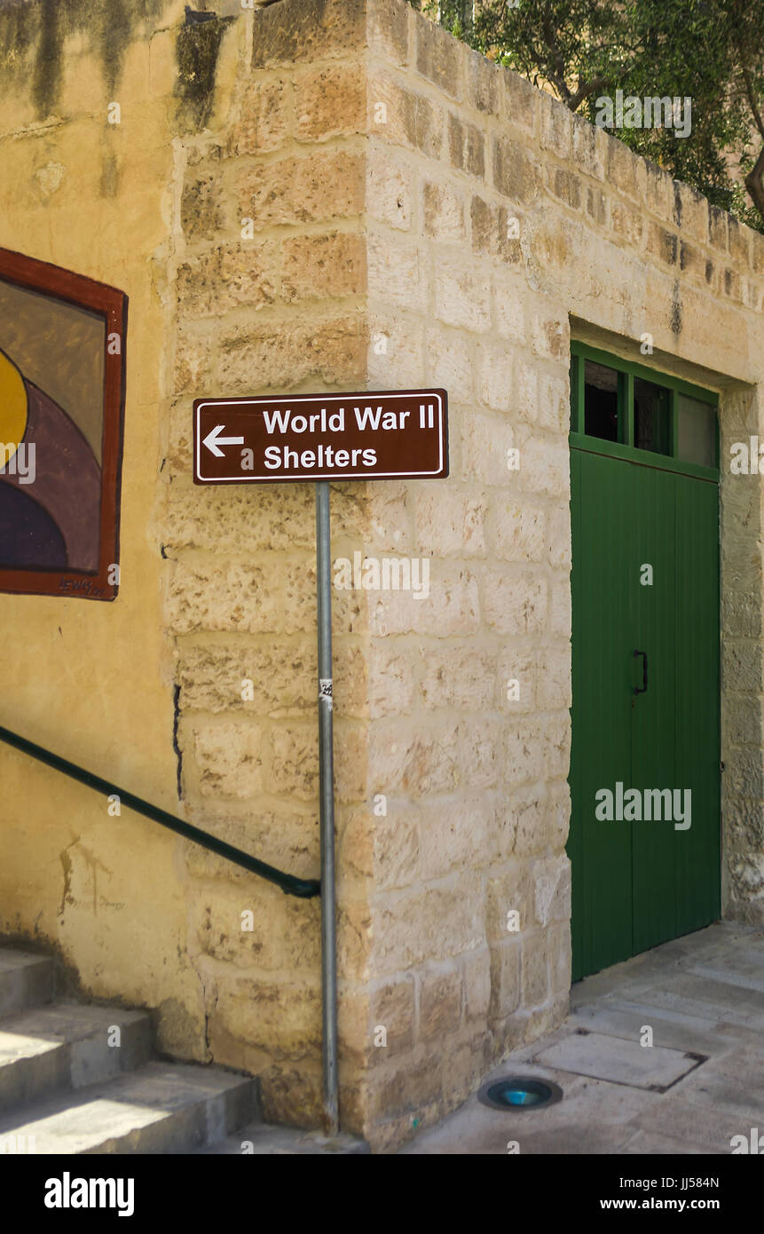 Information sign pointing to air raid shelters - Mellieha, Malta. - Stock Image