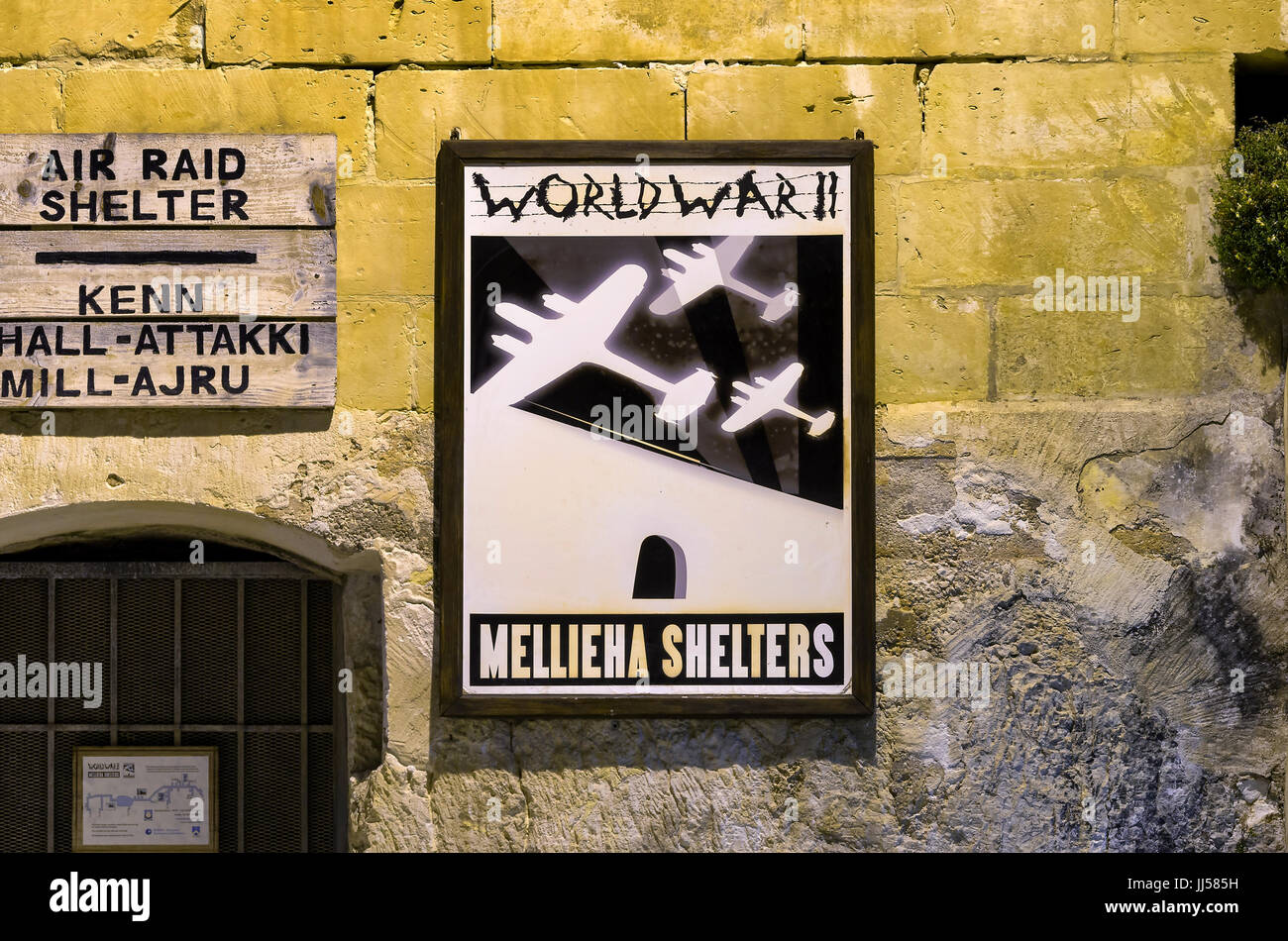 Signboards above the entrance to air raid shelters - Mellieha, Malta. - Stock Image