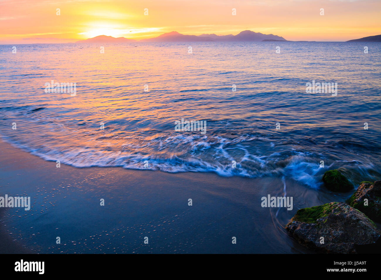 Wonderful sunset behind mountains peak protruding from ocean. Stock Photo